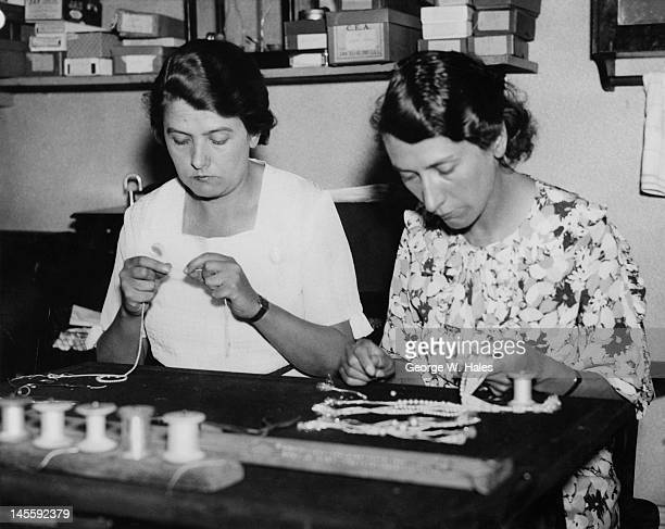 Sisters Ethel and Constance Austen selecting pearls for a necklace at their pearl-stringing business in Hatton Garden, London, 8th August 1935.