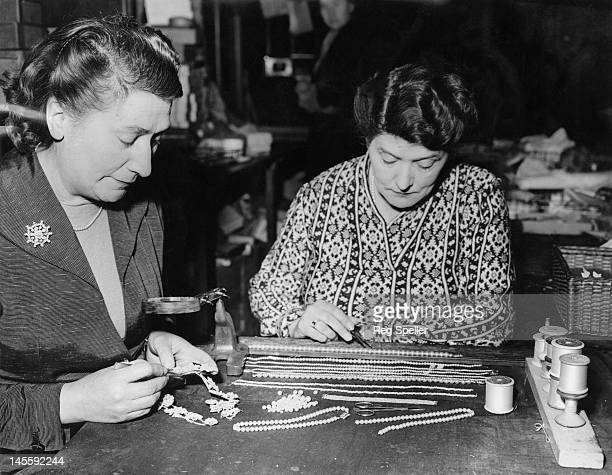 Sisters Ethel and Constance Austen working at their pearl-stringing business in Hatton Garden, London, 13th January 1955. Ethel is re-stringing, on...