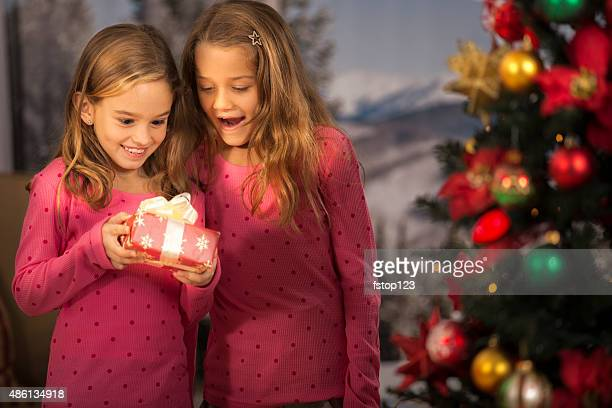 Sisters excited to open Christmas presents. Tree, window background.