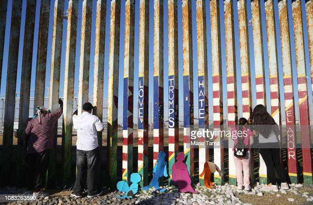Sisters Fernanda and Evelyne Lopez look toward their father standing in San Diego on the other side of the USMexico border fence during the 'Posada...