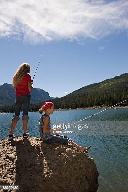 Sisters fishing by lake
