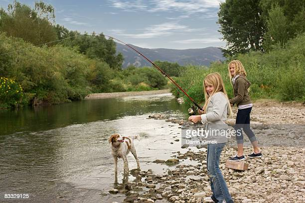 Sisters fishing by river