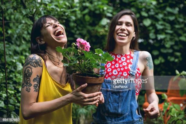 Zusters tuinieren planten in de achtertuin van het huis