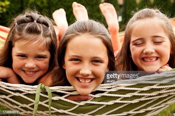 sisters girls school playing hammock outdoors summer elementary age - familie met drie kinderen stockfoto's en -beelden