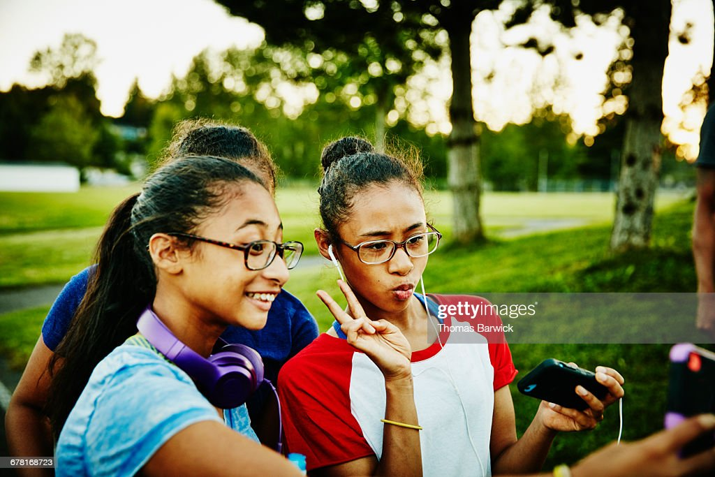 Sisters hanging out and taking selfies at park : Stock Photo