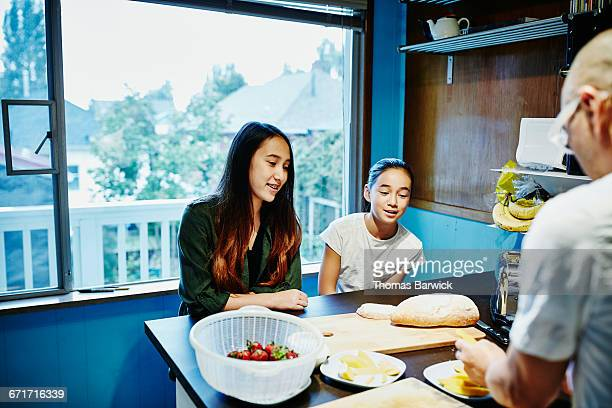 Sisters having breakfast in kitchen before school