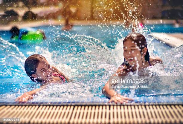 sisters having fun in a swimming pool on a beautiful sunny day - hot teen stock pictures, royalty-free photos & images