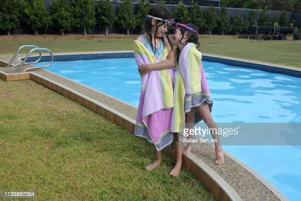 sisters having fun in outdoor swimming pool - rafael ben ari imagens e fotografias de stock