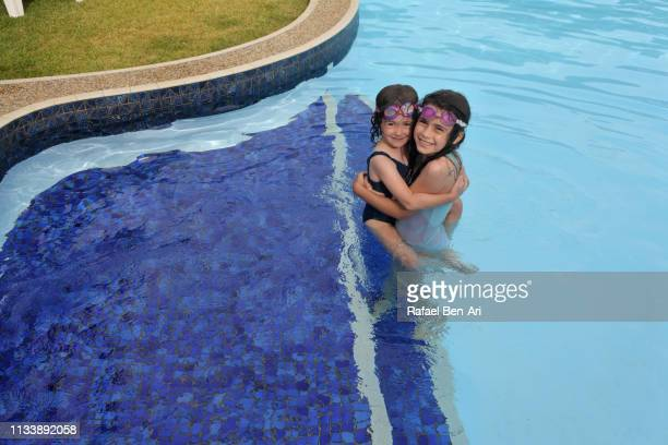 Sisters having fun in outdoor swimming pool