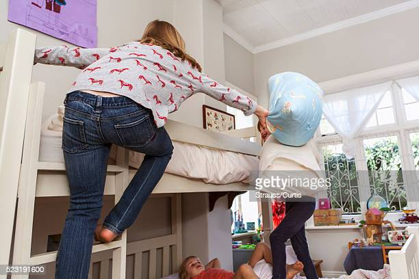 Sisters (6-7, 10-12) having pillow fight in bedroom