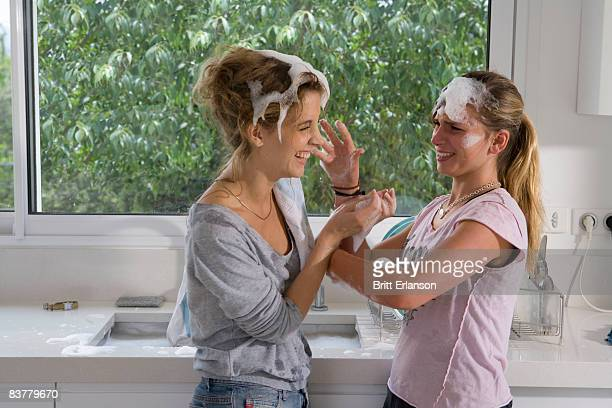 sisters having soap bubble fight at sink - girl fight stock photos and pictures