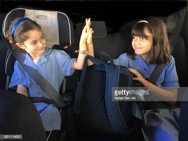 sisters hi five to each other in a car seat on the way to school - rafael ben ari fotografías e imágenes de stock