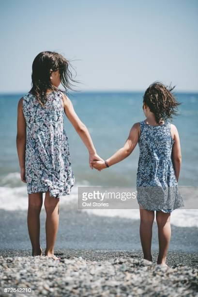 sisters holding hands at the beach - sister stock pictures, royalty-free photos & images