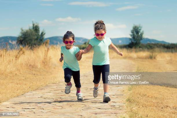 Sisters Holding Hands While Running On Footpath