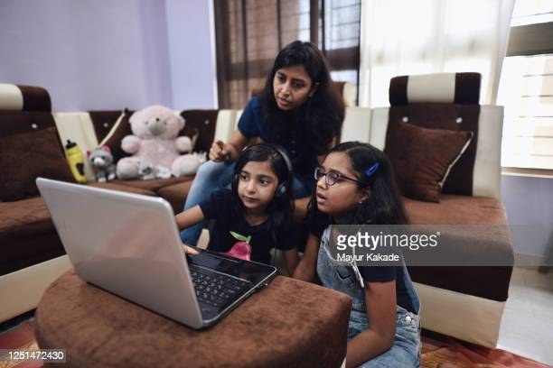 sisters homeschooling using laptop with mother's assistance - homeschool stock pictures, royalty-free photos & images