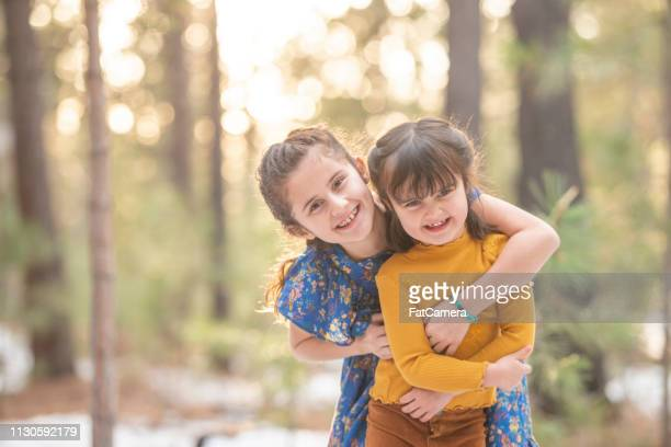 sisters hugging in the woods - sibling stock pictures, royalty-free photos & images