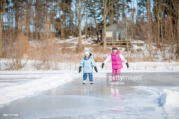 Sisters Ice Skating on Pond
