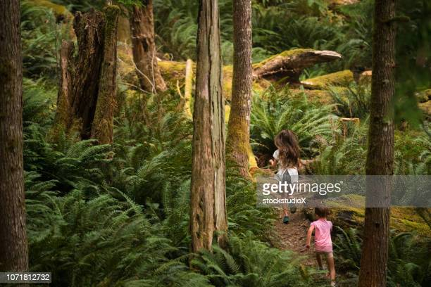sisters immersed in lush nature - vancouver island stock pictures, royalty-free photos & images