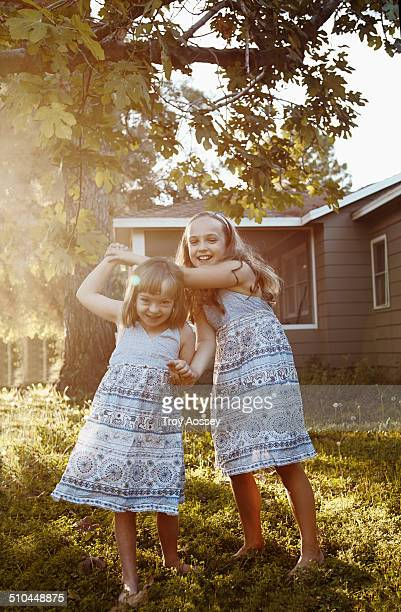 Sisters in blue dresses playing in yard.