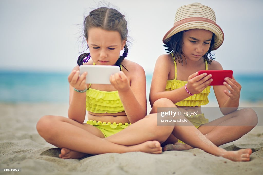 Sisters in conflict are sitting at the beach and sulking each other : Stock Photo
