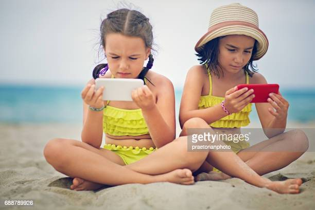 Sisters in conflict are sitting at the beach and sulking each other