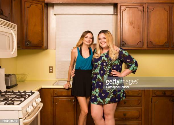sisters in grandmother's empty kitchen - fat girls stock photos and pictures