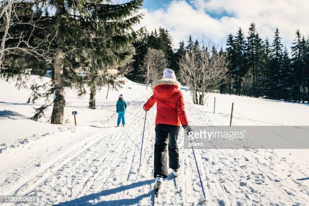 sisters in snowy winter landscape on cross-country-ski - czech republic stock pictures, royalty-free photos & images