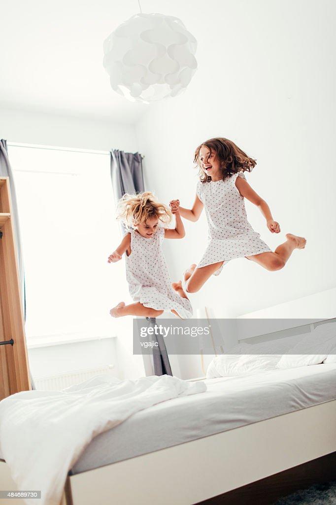 Hermanas salto sobre la cama. : Foto de stock