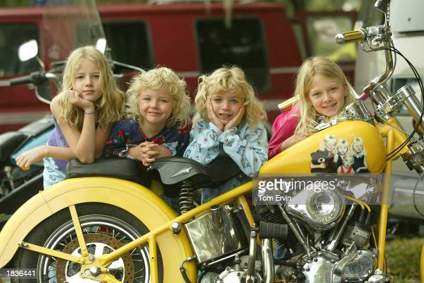 Sisters Karly Walsh 9yearsold Kamary Walsh 5yearsold McKenzy Walsh 7yearsold and Kaytlin Kelly 11yearsold lean on their dad's motorcycle at a biker...