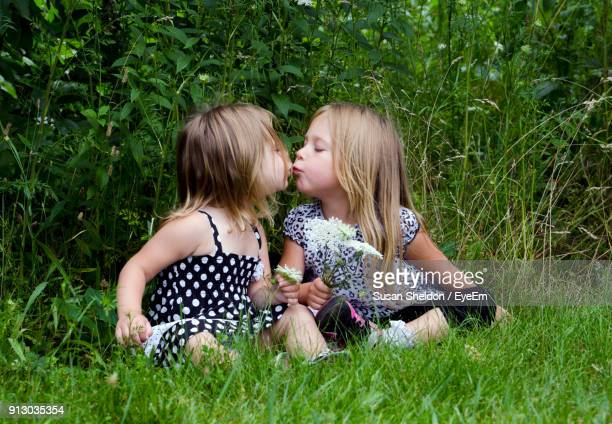 Sisters Kissing While Sitting On Grassy Field