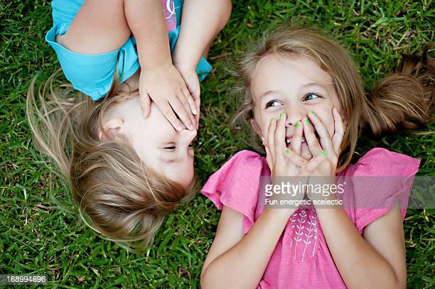sisters laughing on grass