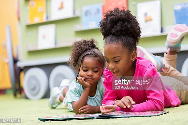 sisters laying on the library floor reading books - sibling stock pictures, royalty-free photos & images