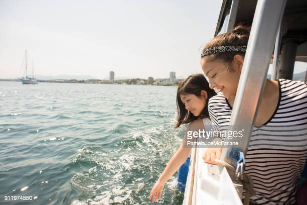 Sisters Lean, Reach Out to Touch Water on Boat Ride_WF.jpg