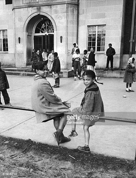 Sisters Linda and Terry Lynn Brown sit on a fence outside of their school the racially segregated Monroe Elementary School Topeka Kansas March 1953...