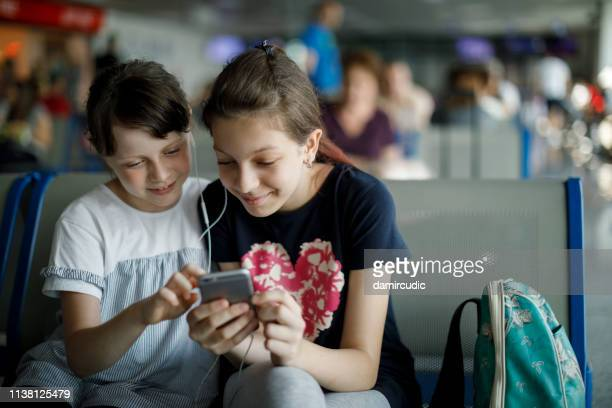 sisters listening to music at airport lounge - damircudic stock photos and pictures