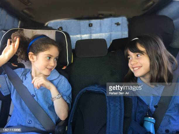 sisters looking at each other in a car seat on the way to school - rafael ben ari - fotografias e filmes do acervo