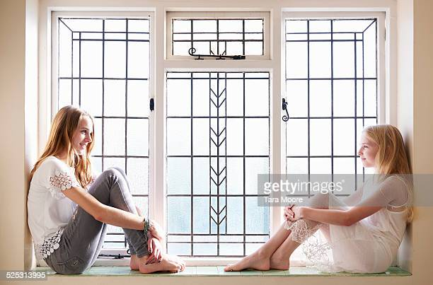 sisters looking at each other - girls barefoot in jeans stock photos and pictures