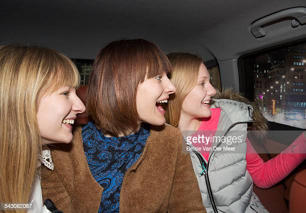 sisters looking out of car window at night. - only young women stock pictures, royalty-free photos & images