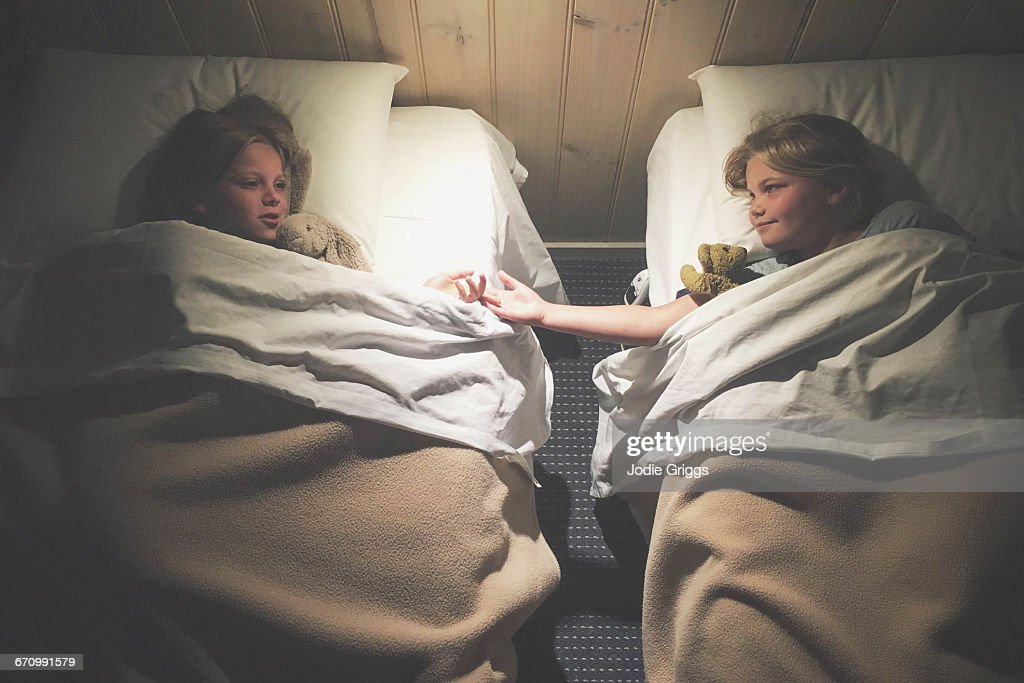 Sisters lying in separate beds talking together : Stock Photo