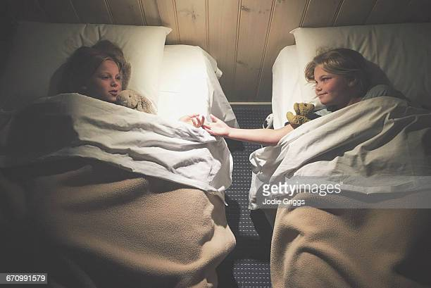 Sisters lying in separate beds talking together
