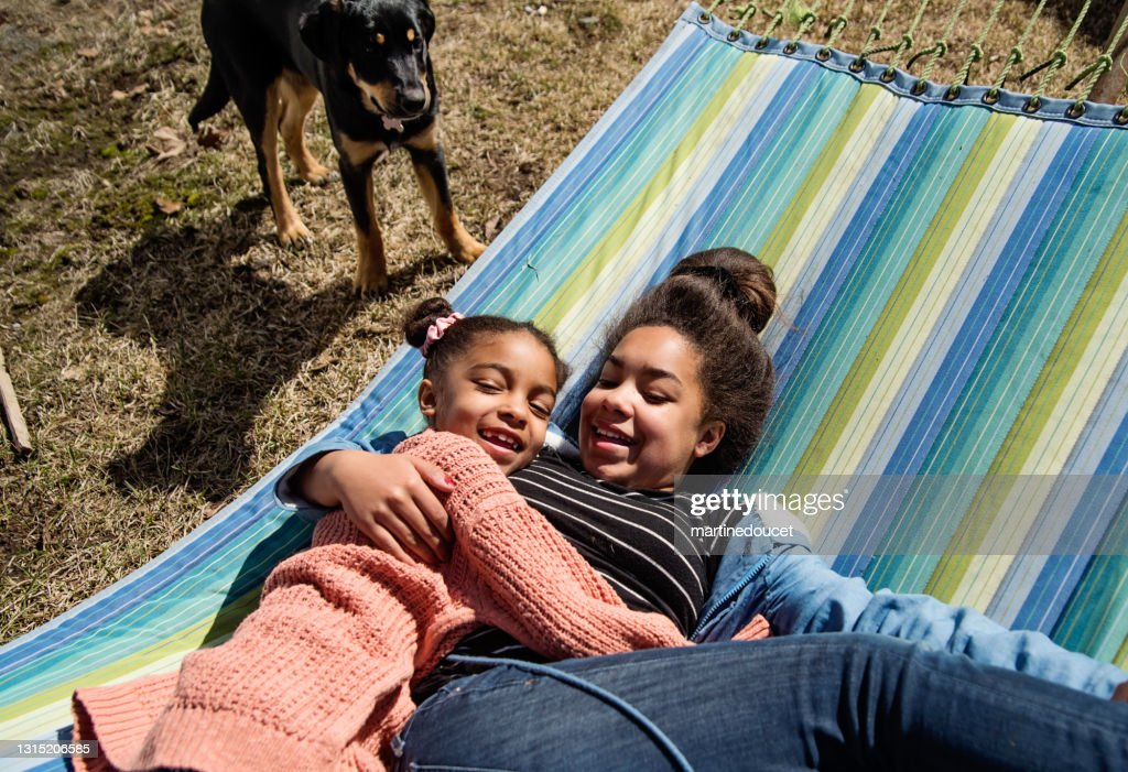Sisters lying on hammock outdoors in springtime. : Stock Photo