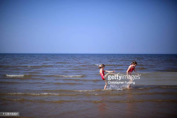 Sisters Madeline aged 10 and Tabatha Wise aged six take to sea under a cloudless sky at Ainsdale beach on April 19 2011 in Ainsdale United Kingdom...