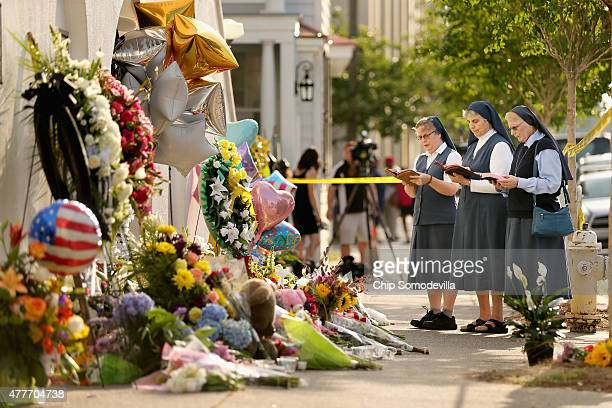 Sisters Margaret Kerry, Mary Thecla and Kathleen Lang of the Order of the Daughters of St. Paul pray outside the historic Emanuel African Methodist...