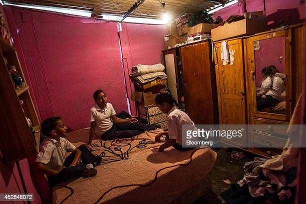 Sisters Natali Graterol center Niurka Susana Graterol left and Edith Yorleni Graterol sit in their bedrom in their home constructed of sheet metal on...