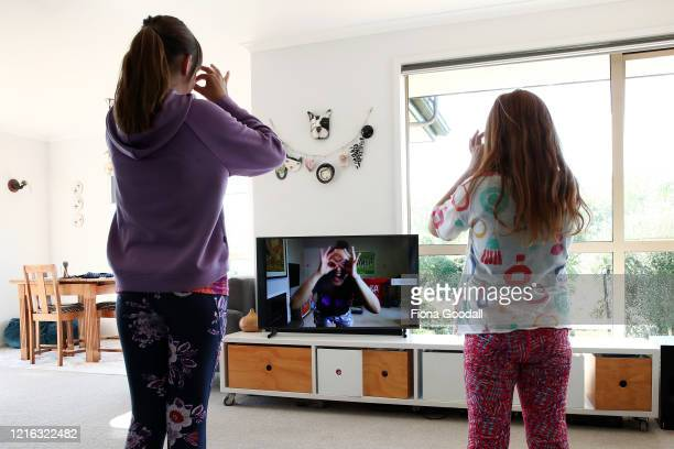 Sisters Nina Goodall and Ivy Goodall who are related to the photographer follow a Zumba lesson online at their home in Kaipara Flats on April 02 2020...