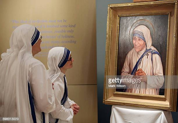 Sisters of the Missionaries of Charity look at the official canonization portrait of Mother Teresa during a portrait unveiling ceremony at The Saint...