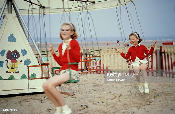 sisters on swing at beach funfair - 1967 stock pictures, royalty-free photos & images