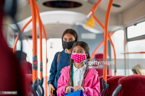 sisters on the bus during a pandemic - primary school child stock pictures, royalty-free photos & images