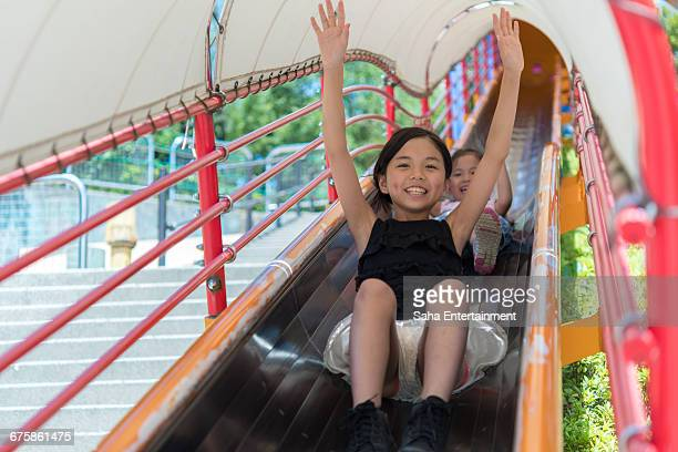 sisters play on the slide - saha entertainment stock pictures, royalty-free photos & images