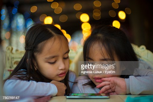 Sisters Playing Game On Mobile Phone At Home During Night